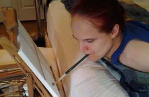 Disabled artist painting on canvas.